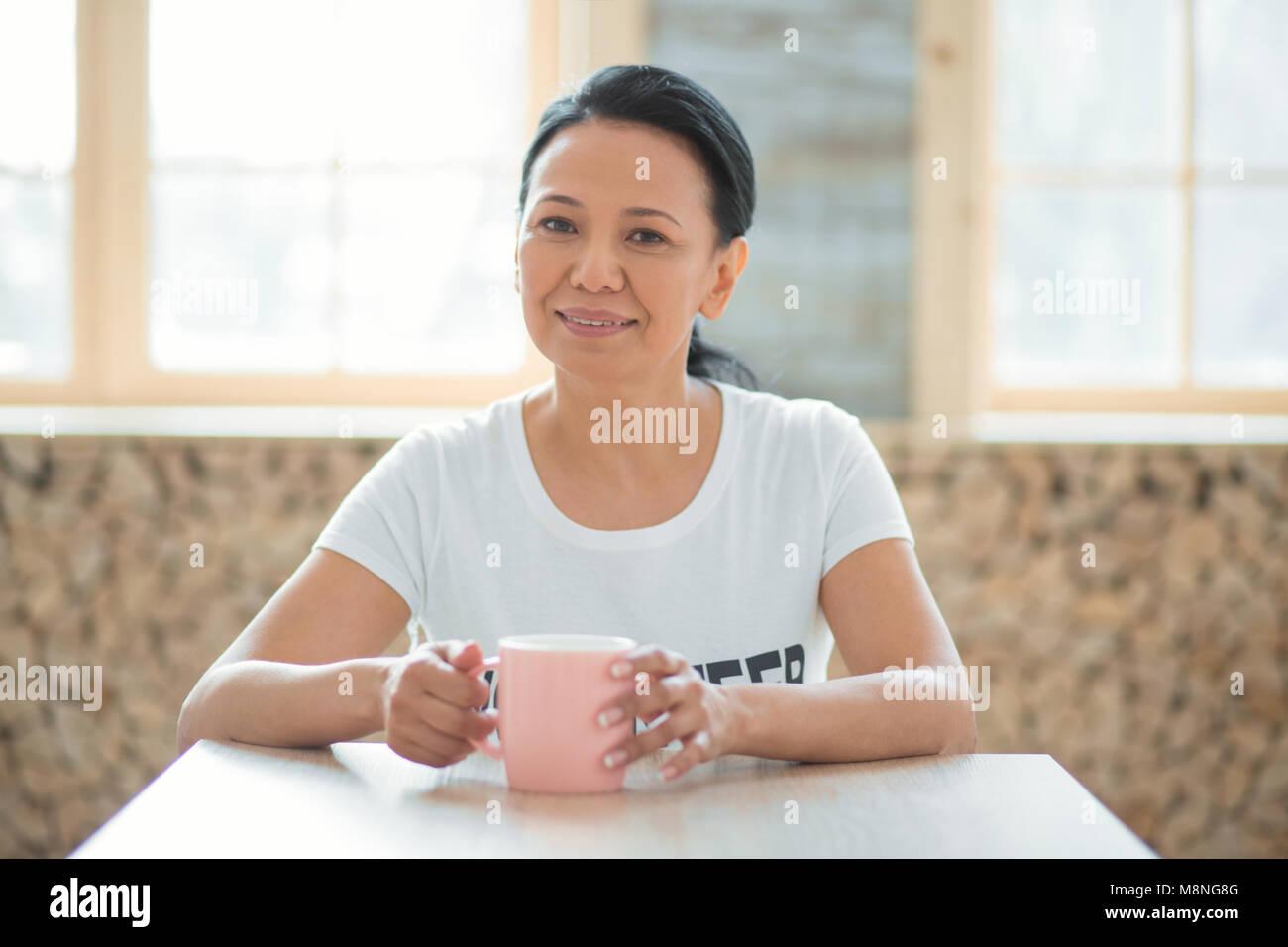 Appealing female volunteer drinking coffee - Stock Image