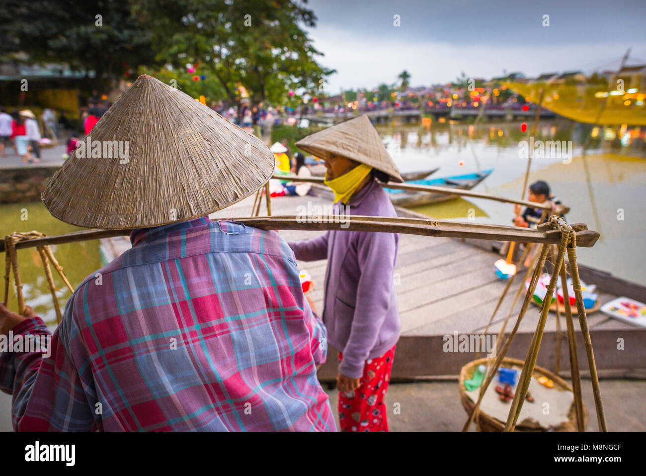 Vietnam women, two female vendors wearing Vietnamese conical hats chat along the waterfront in Hoi An, Central Coast, - Stock Image