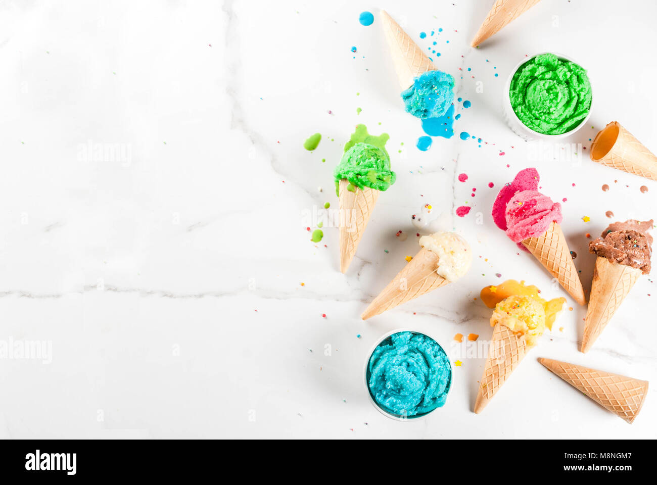Different homemade melting ice cream in bowls and waffle ice cream cones, white vanilla, orange, pink berry, green, - Stock Image