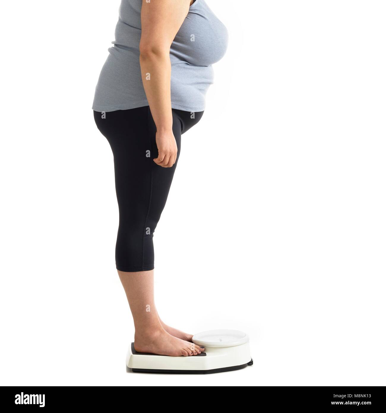 Overweight woman standing on weighing scales. - Stock Image