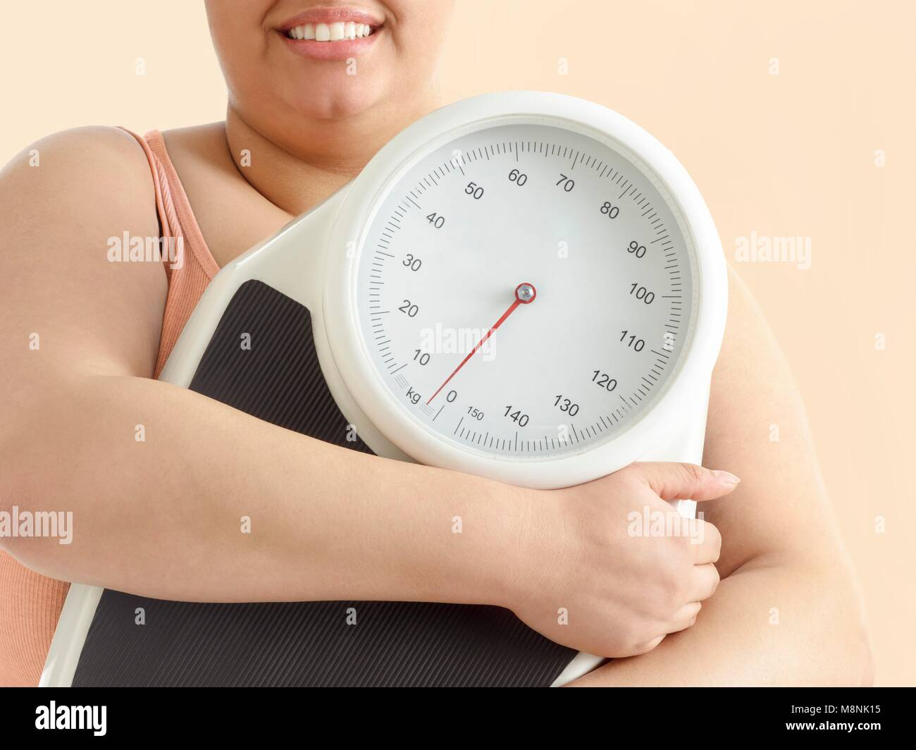 Overweight woman holding weighing scales, smiling. - Stock Image
