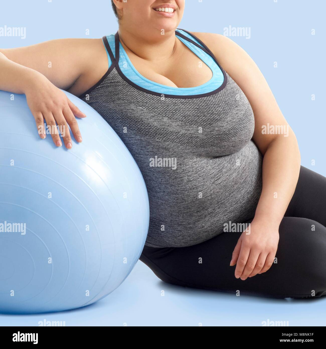 Overweight woman resting against exercise ball. - Stock Image