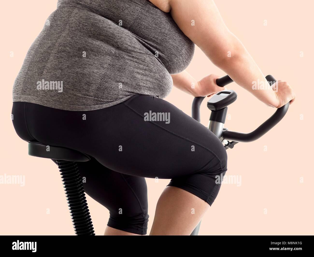 Overweight woman on exercise bike. - Stock Image