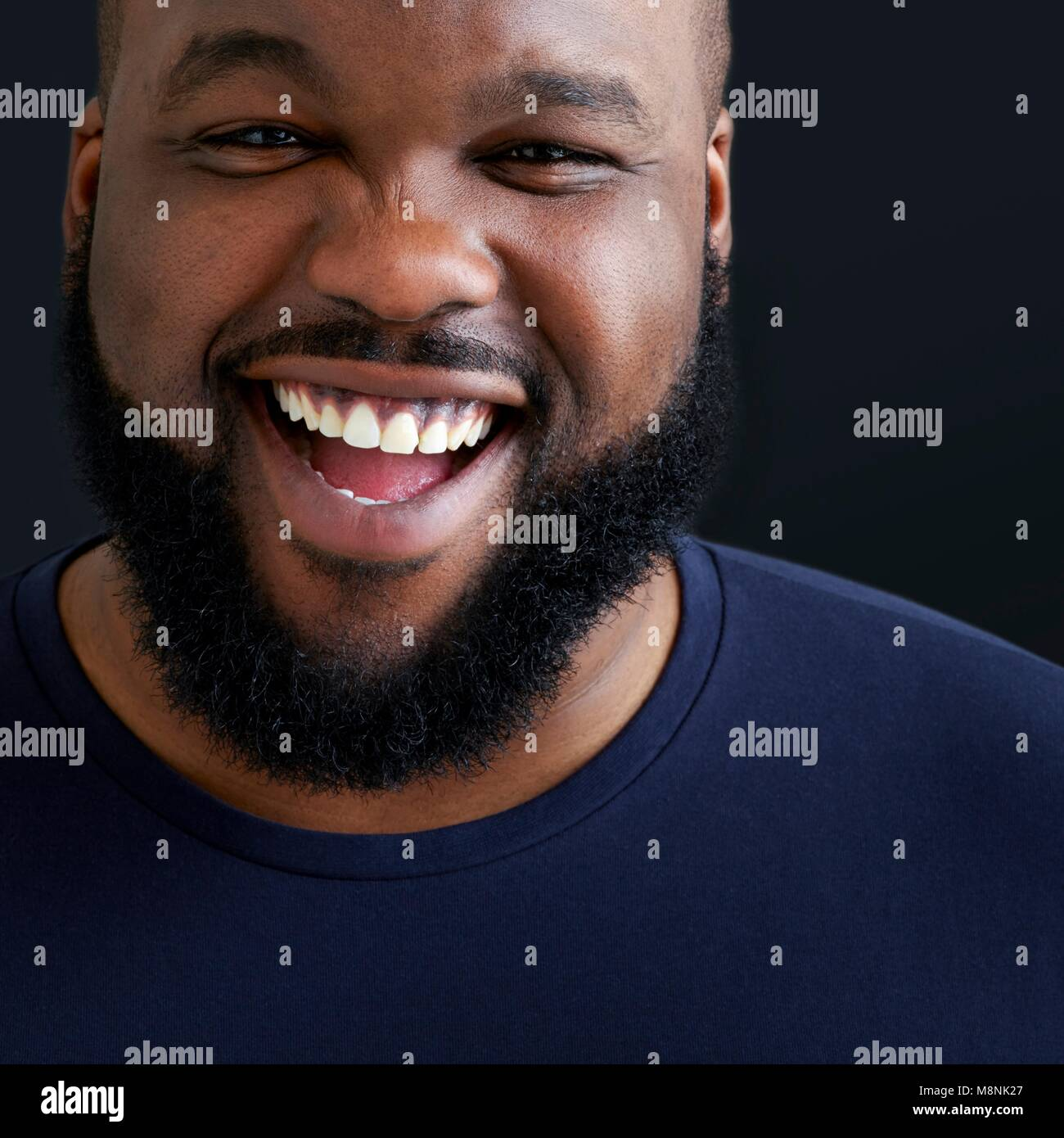 Close up of man laughing and smiling towards camera. Stock Photo
