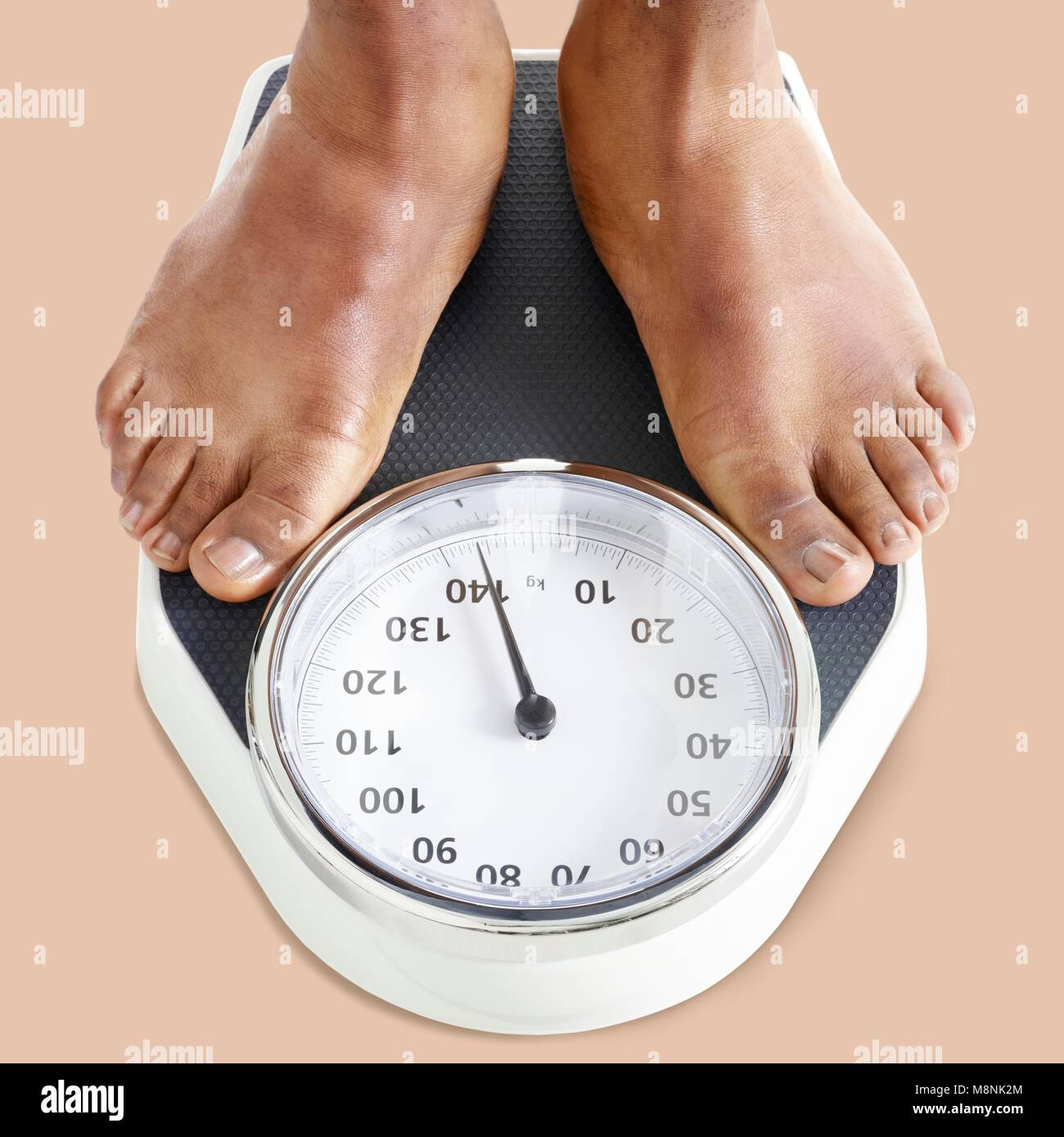Man standing on weighing scales. - Stock Image
