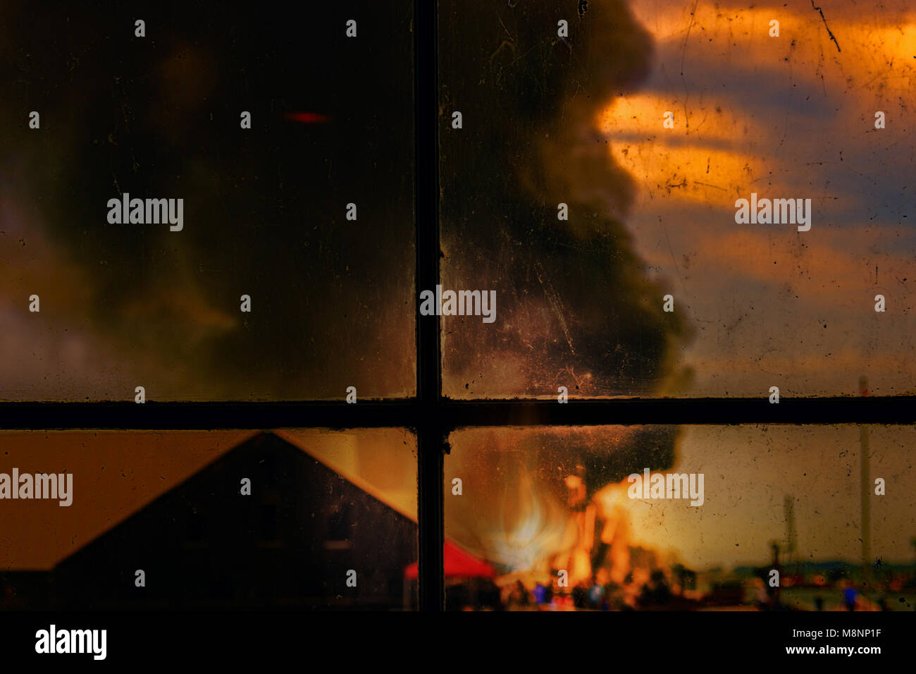 view from a window on a burning house, smoke and flames of fire, people silhouettes, soot on the glass and in the - Stock Image