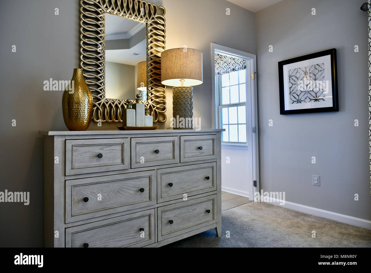 Modern Bedroom Dresser With Gold Accented Decor And Mirror Above Stock Photo Alamy