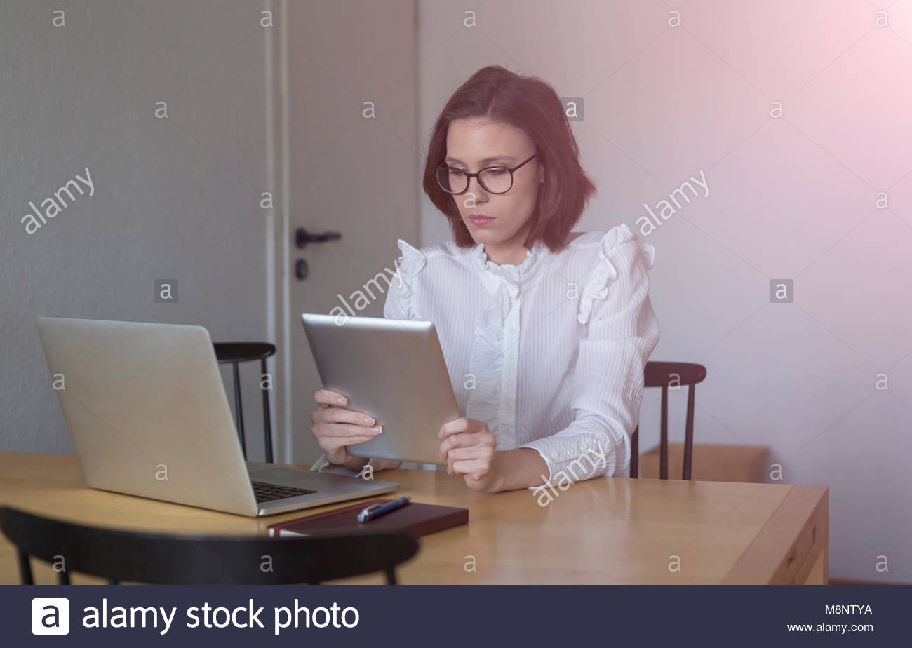 Young businesswoman or female entrepreneur sitting at a table working from home with an open laptop as she reads - Stock Image