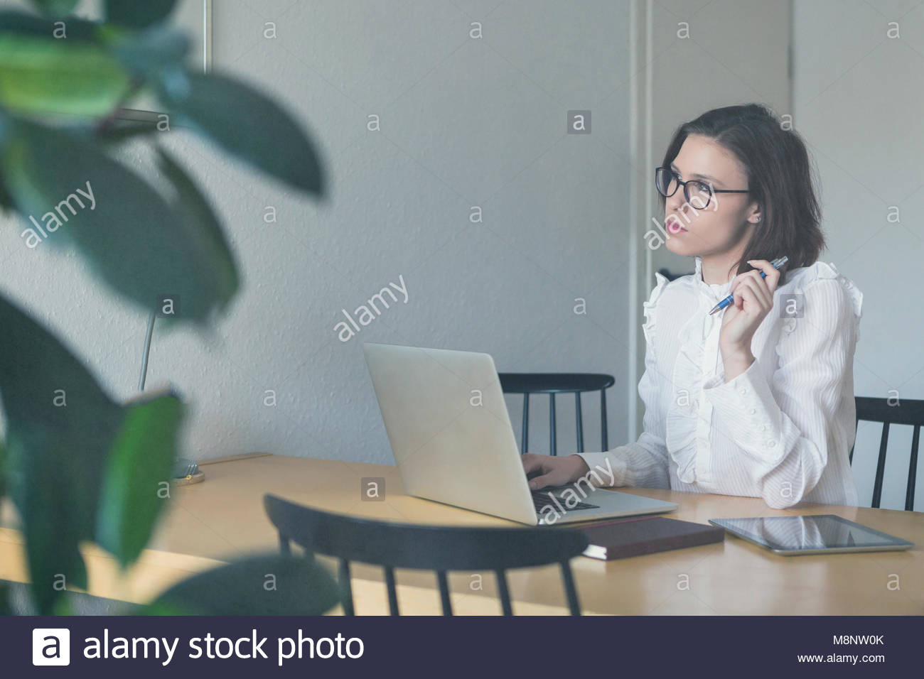 Young female entrepreneur working from home seated in a home office at a wooden table typing on a laptop computer - Stock Image