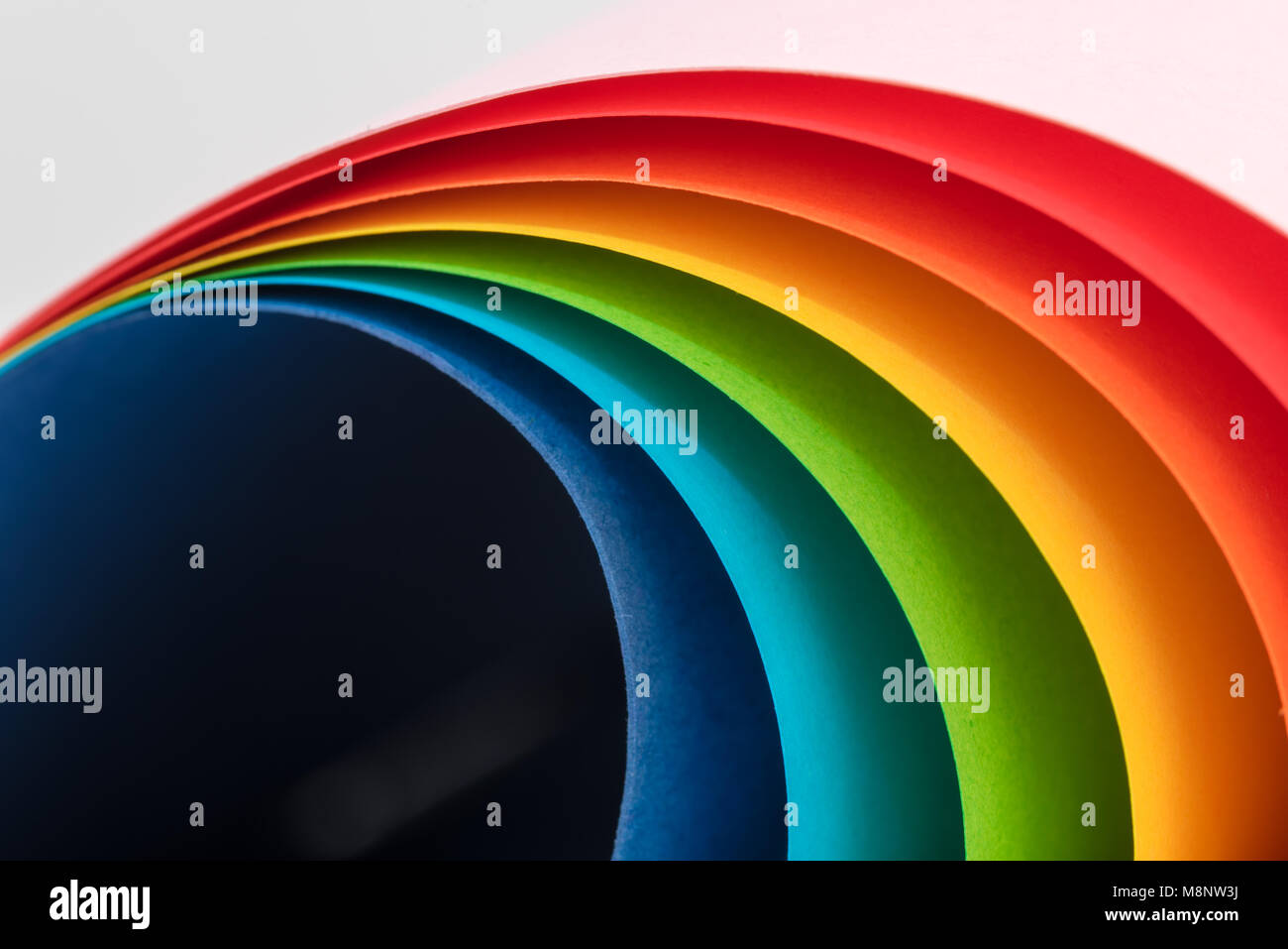 Rainbow of sheets of coloured card forming a gentle curve - Stock Image
