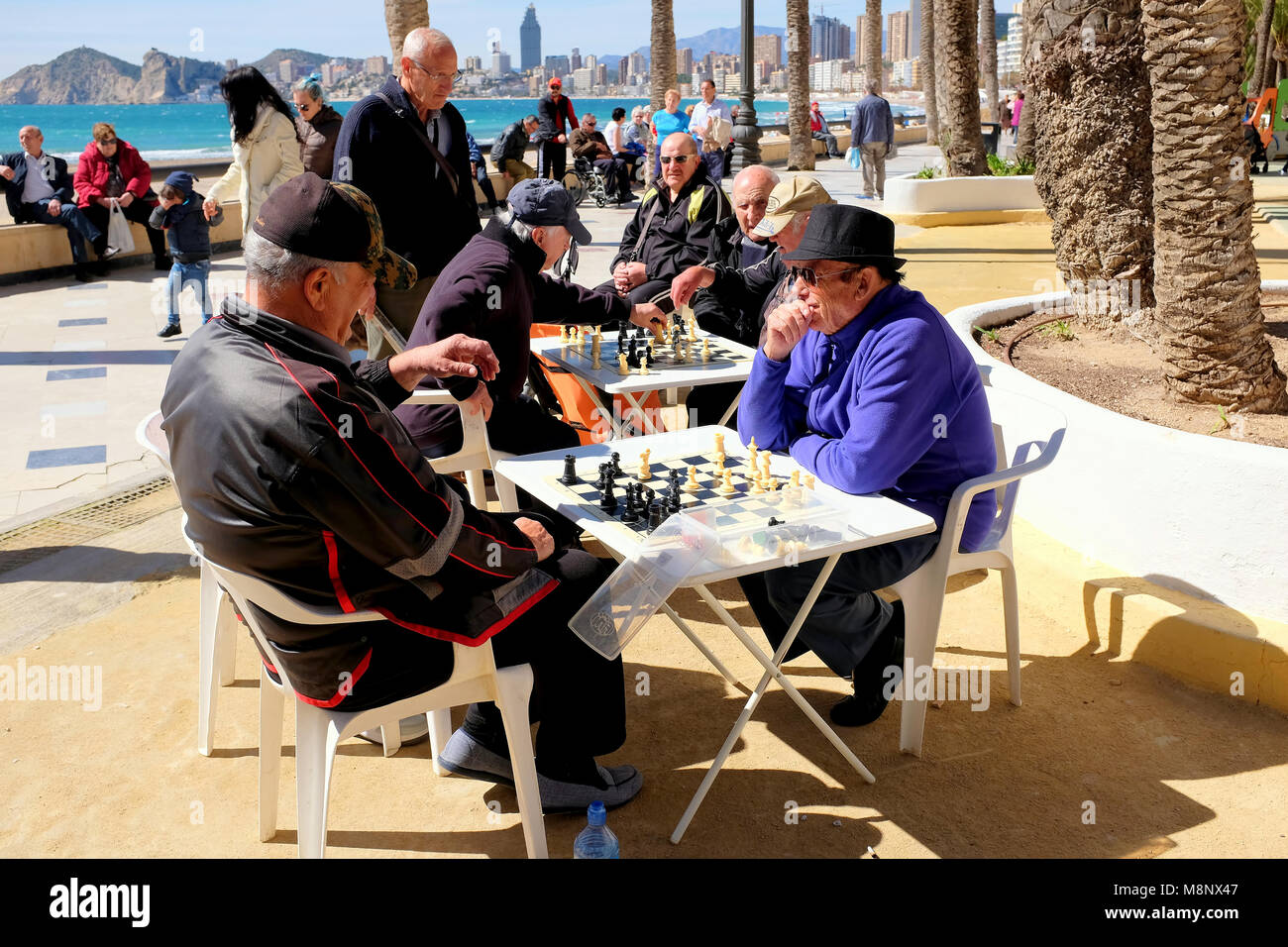 Benidorm, Spain.  March 07, 2018.  Holidaymakers walk the promenade as the Spanish locals play Chess under the palms - Stock Image