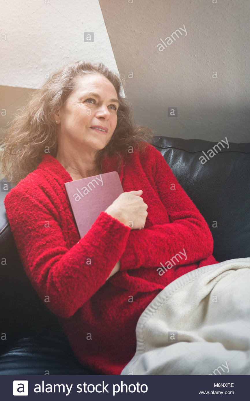 Mature attractive woman in a colorful red sweater sitting relaxing on a sofa under a warm rug daydreaming clutching - Stock Image