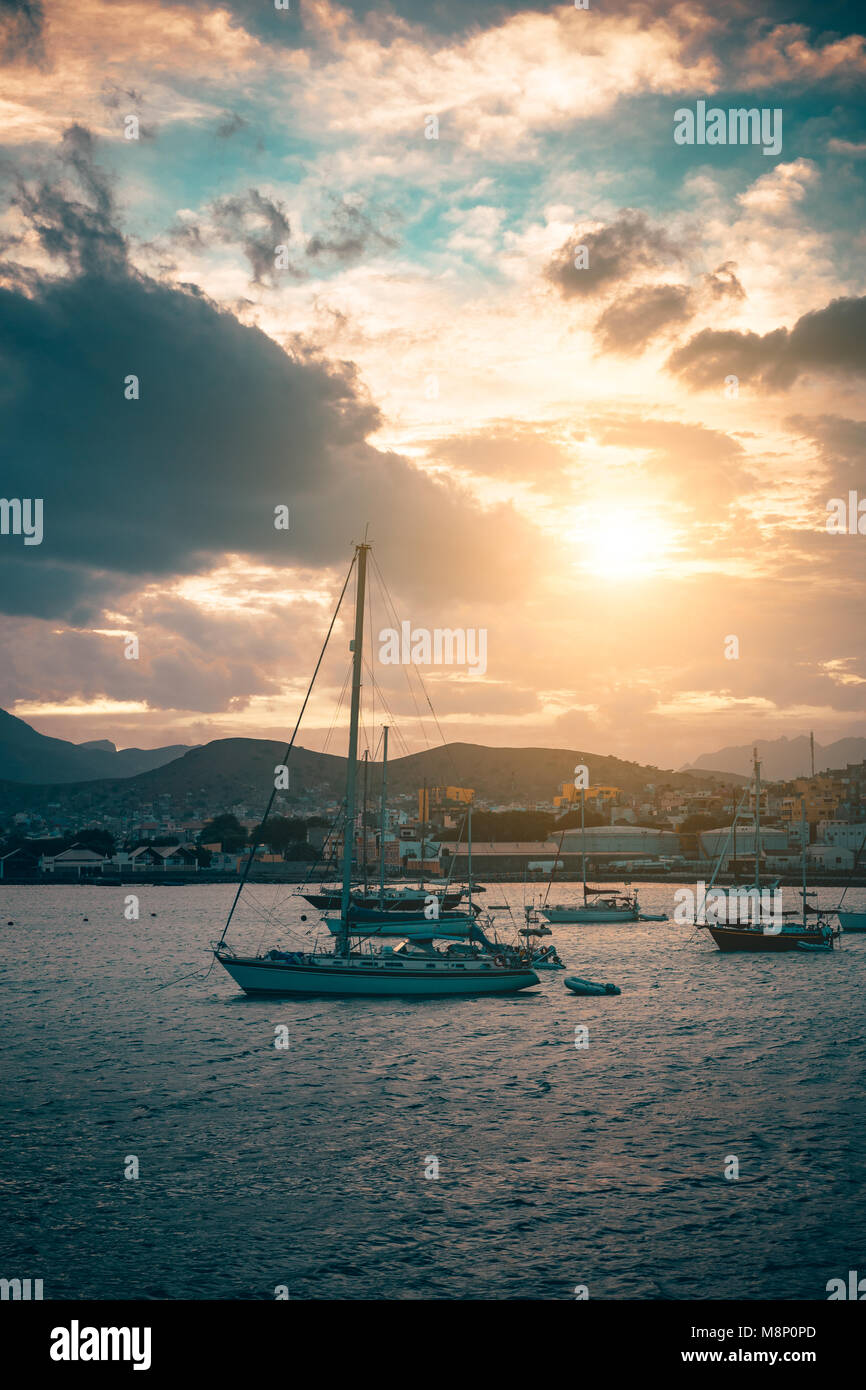 Sail Yacht on anchor in Mindelo Harbor on sunset. Golden flares light the cloudy sky. Sao Vicente Island, Cape Verde Stock Photo