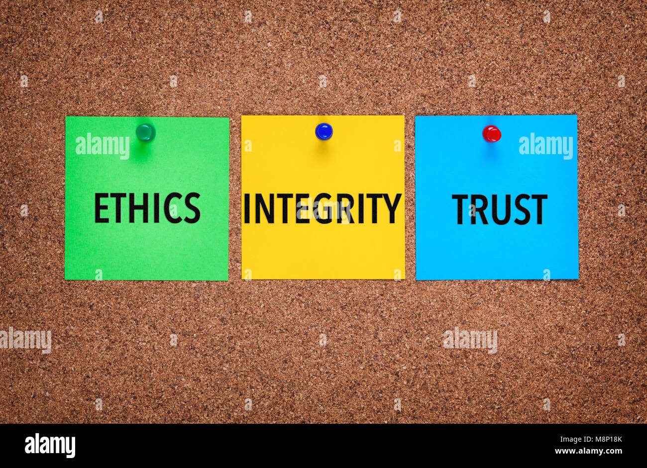 Three notes on corkboard with words Integrity, Trust, Ethics. Close-up. - Stock Image