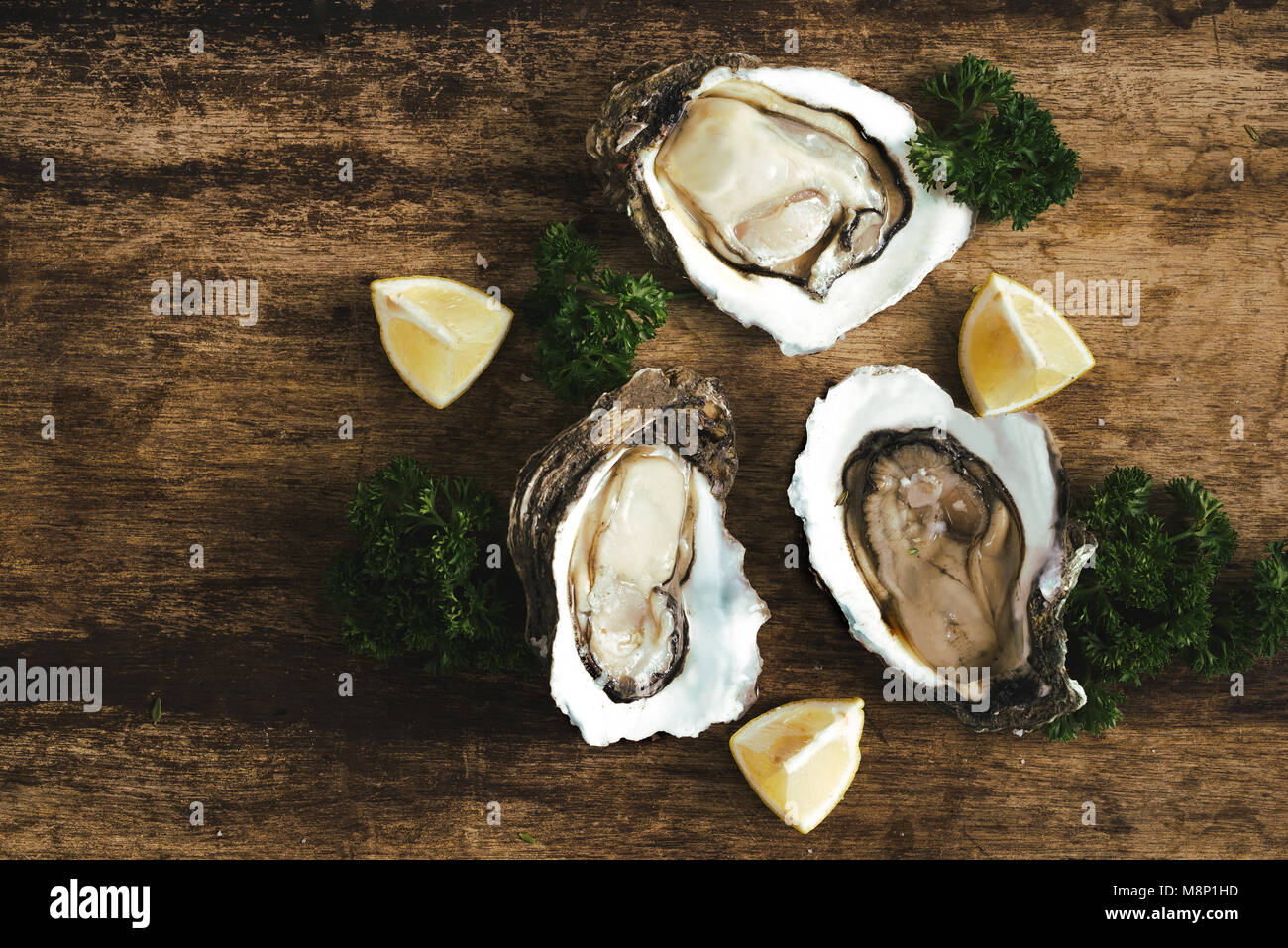 fresh just opened oysters and slice of lemon on rustic wooden background - Stock Image