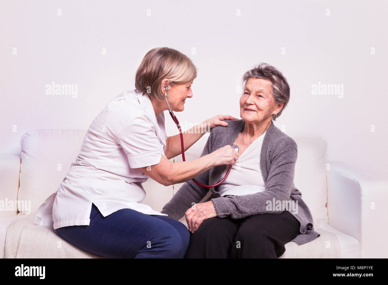 Studio portrait of a senior nurse examining an elderly woman. - Stock Image