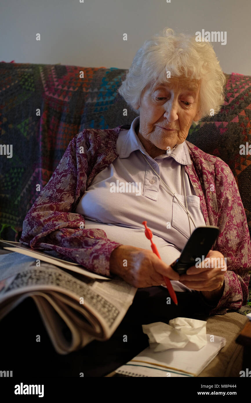 An old-age pensioner texting on her phone. - Stock Image