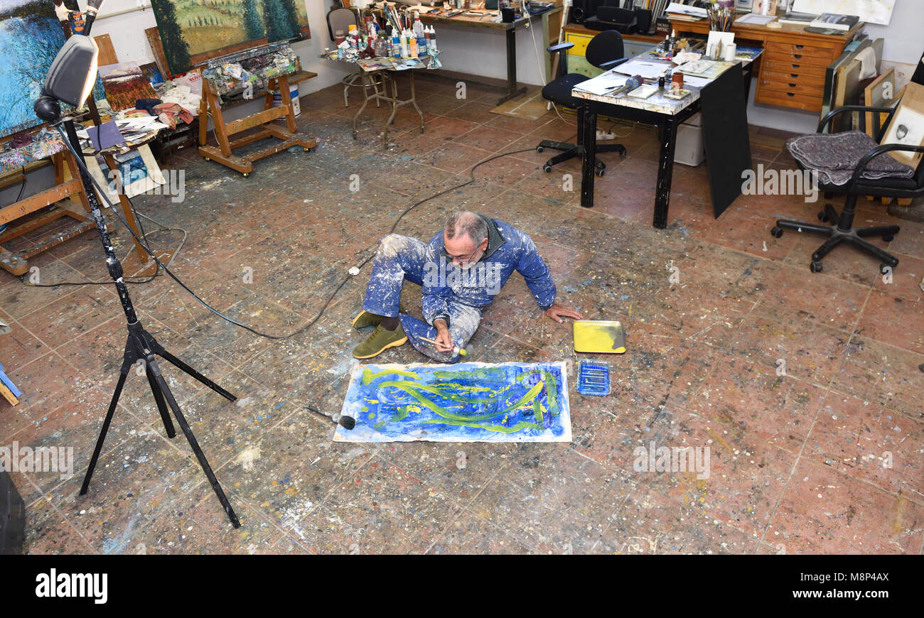 portrait of a painter artist who works in his studio - Stock Image