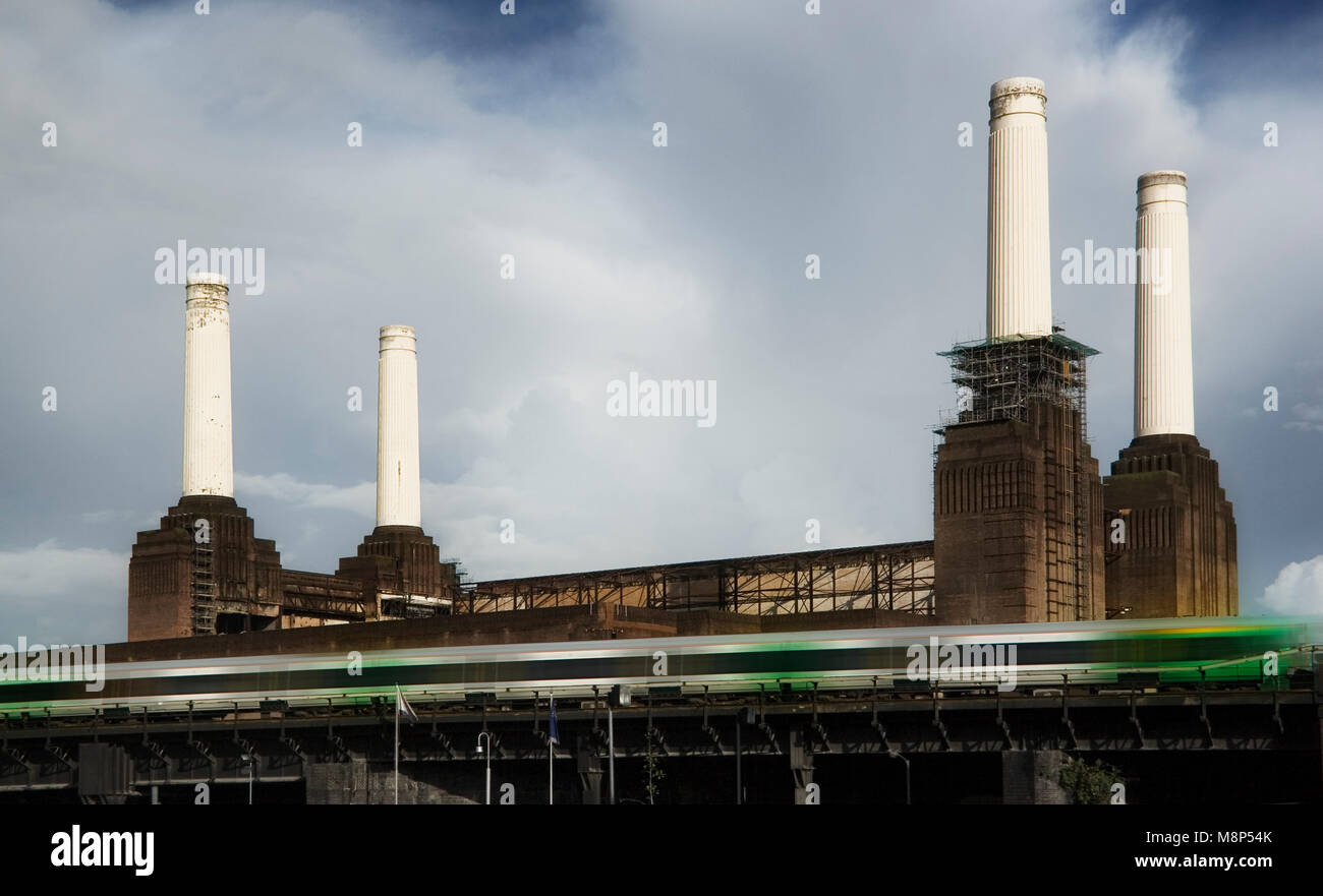Four chimneys of decommissioned coal Battersea power station with green tube train moving fast in foreground - Stock Image