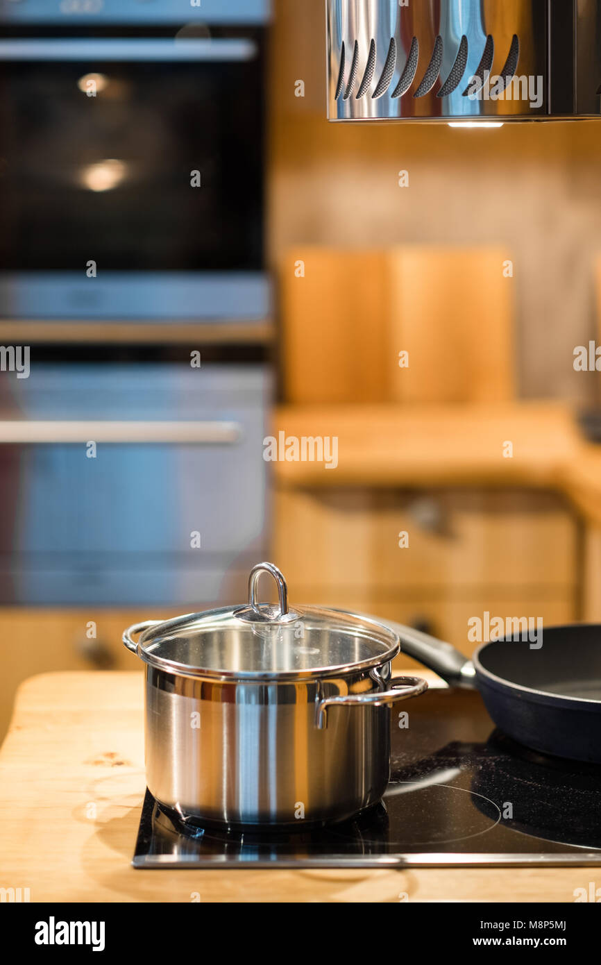 Modern kitchen interior in bright wood optics with cooking pot, pan and stainless steel appliances and extractor - Stock Image