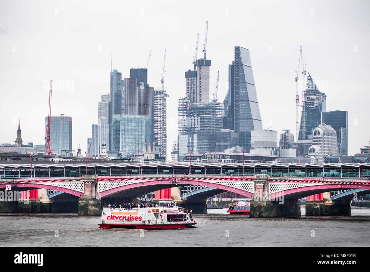 Blackfriars foot bridge in front of the Blackfriars railway bridge over the river Thames, with city of London financial Stock Photo