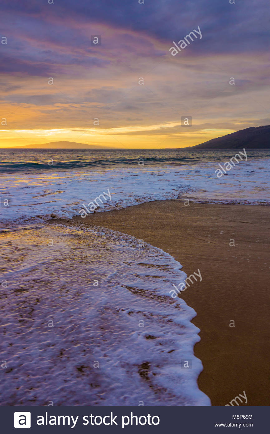 Sunset reflected in a gentle Pacific surf on Kamaole Beach Park 11 in Kihei on the island of Maui in the state of Stock Photo