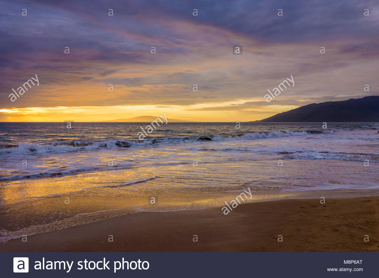 Sunset reflected in a gentle Pacific surf on Kamaole Beach Park 11 in Kihei on the island of Maui in the state of - Stock Image