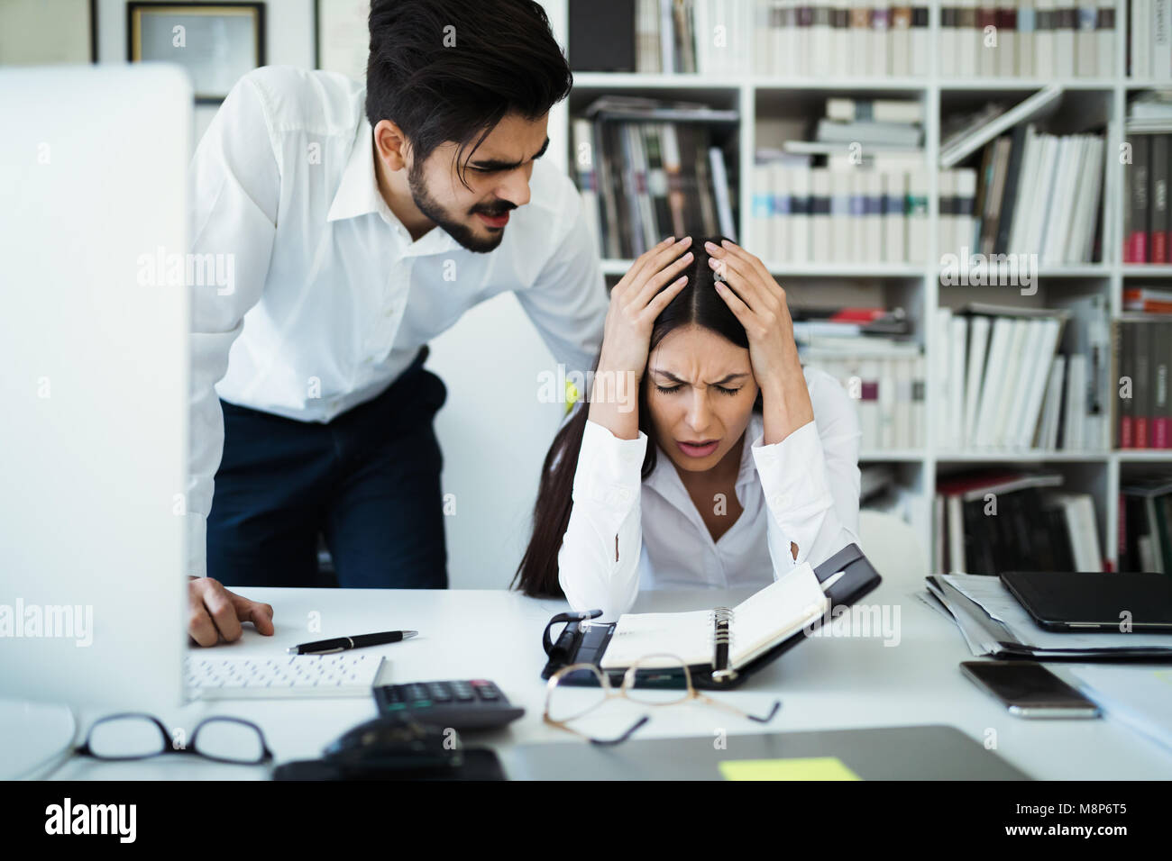 Angry irritated boss reprimanding employee afraid to be fired, accusing of mistake in report, bad work - Stock Image