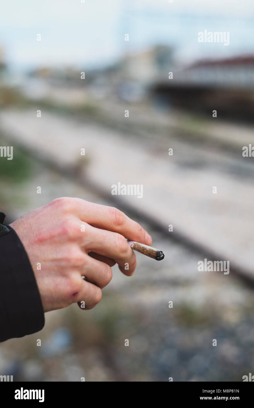 closeup of a young caucasian man outdoors smoking a hand-rolled cigarette or a joint - Stock Image