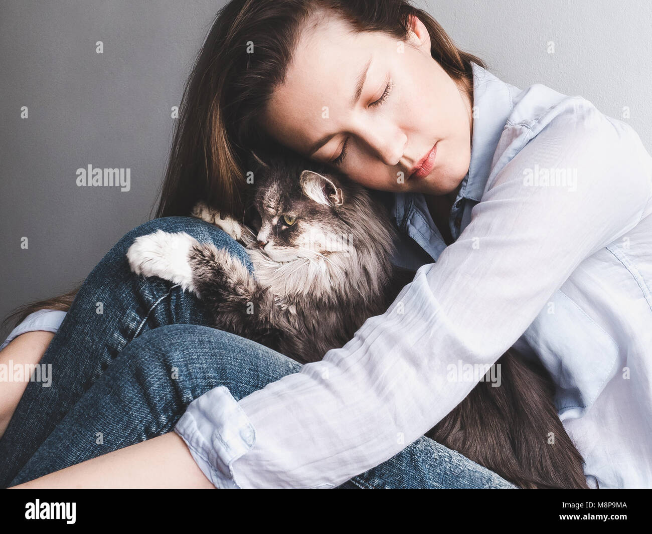 Stylish woman gently hugging kitten - Stock Image