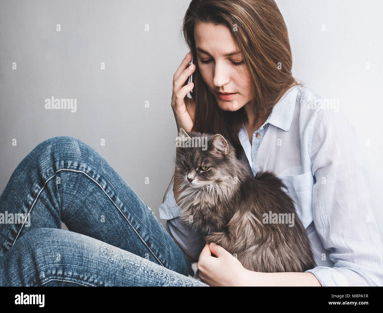 Young woman gently holding a kitten - Stock Image