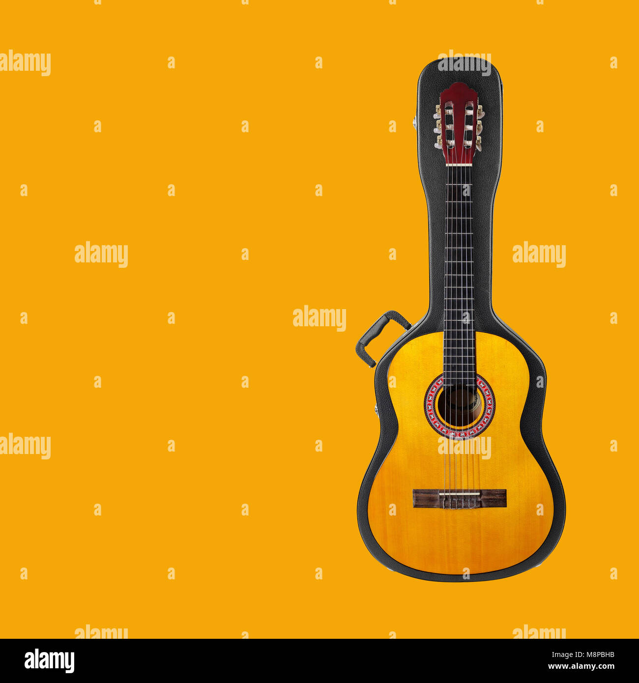 Musical instrument - Acoustic classic guitar from above on a hard case on a yellow background. Stock Photo