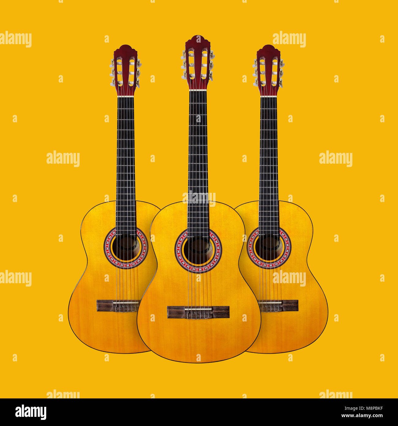 Musical instrument - Three Classic guitar on a yellow background. - Stock Image