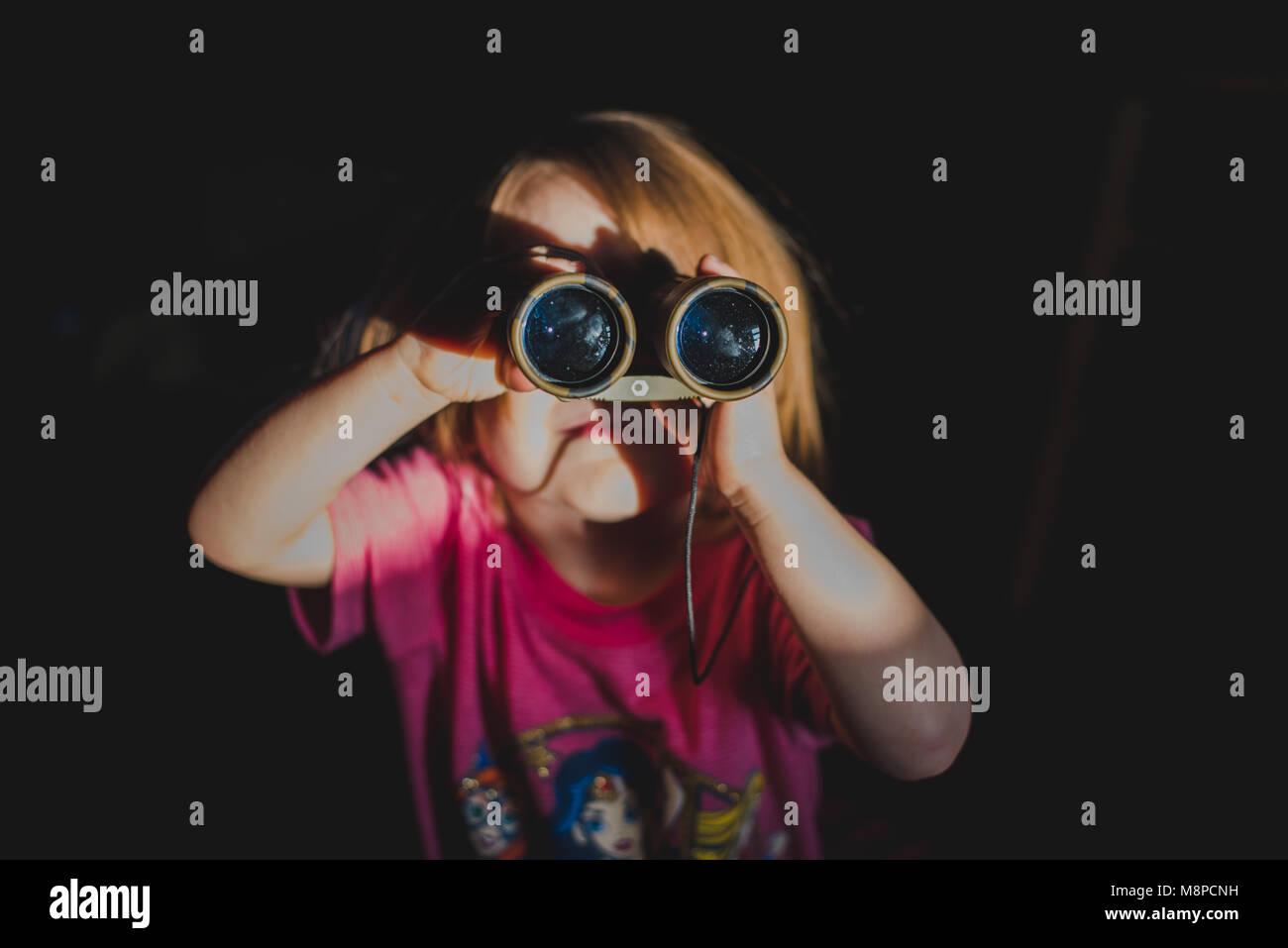 A young toddler girl looking through binoculars. Stock Photo