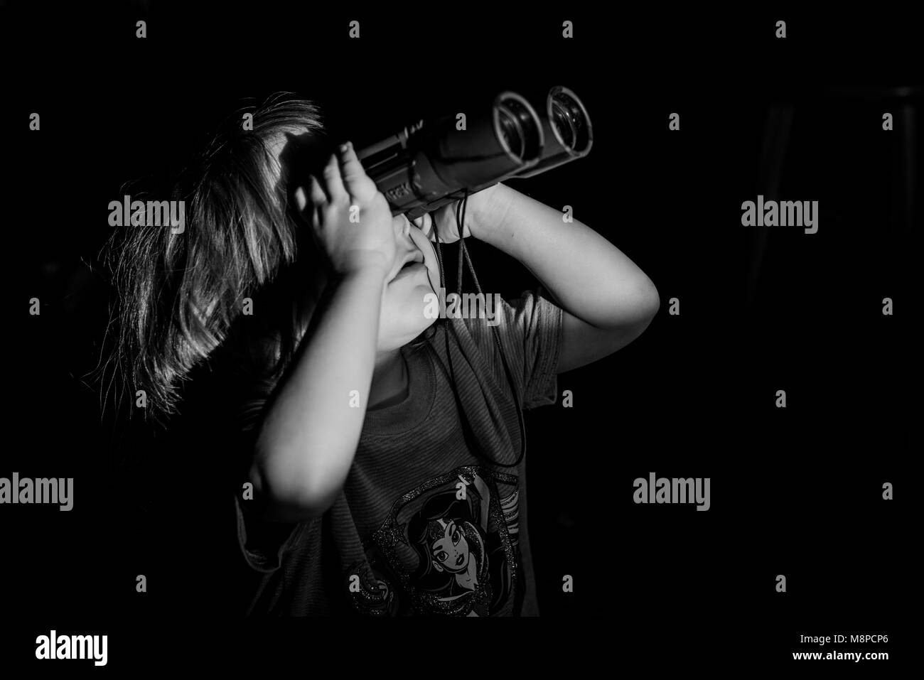 A young toddler girl looking through binoculars. - Stock Image