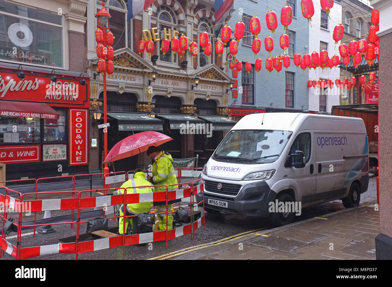 BT Open Reach engineers in the rain in Soho, London. - Stock Image