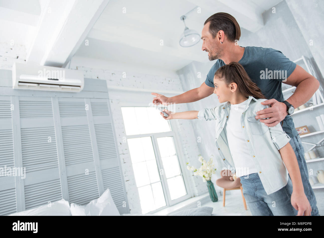 Positive joyful man pointing at the air conditioner - Stock Image