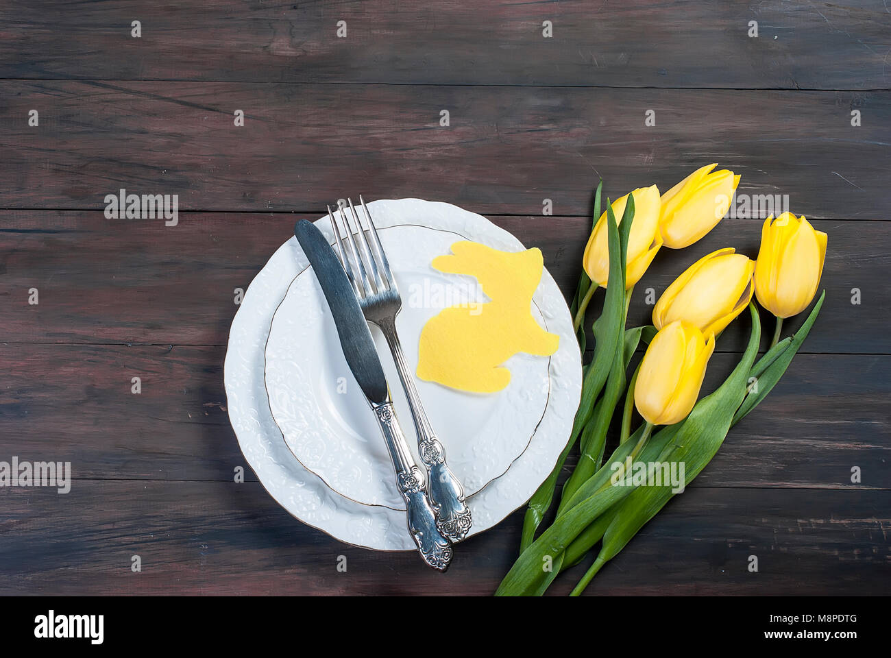 Place Setting for Easter, olored easter eggs and  bouquet of yellow tulips on a wooden background Stock Photo