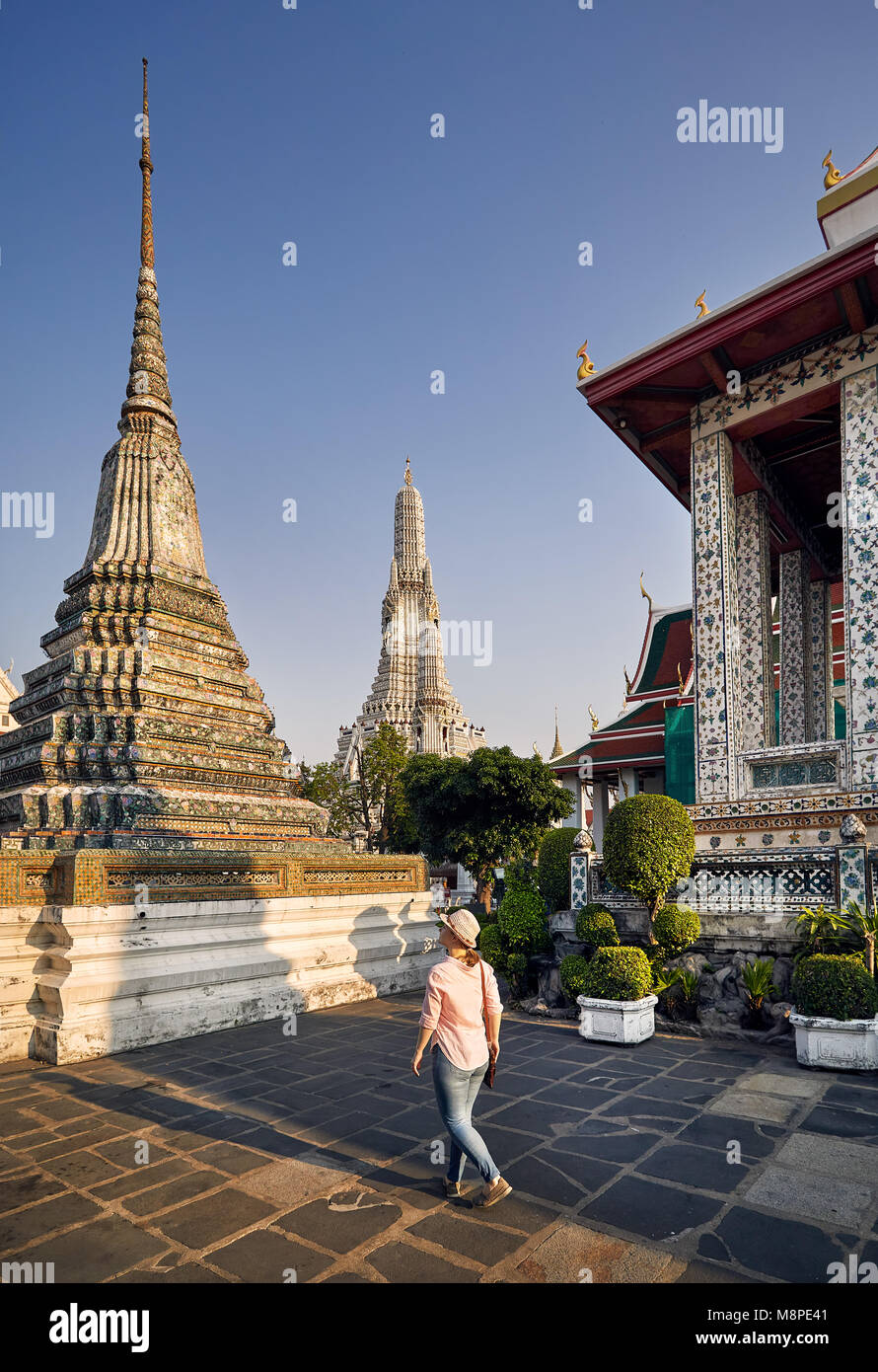 Beautiful tourist woman in hat and pink shirt walking in Wat Arun temple at sunset in Bangkok, Thailand. Stock Photo