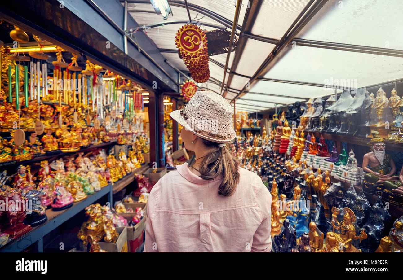 Tourist woman in hat and pink shirt at market with souvenirs in Bangkok, Thailand - Stock Image