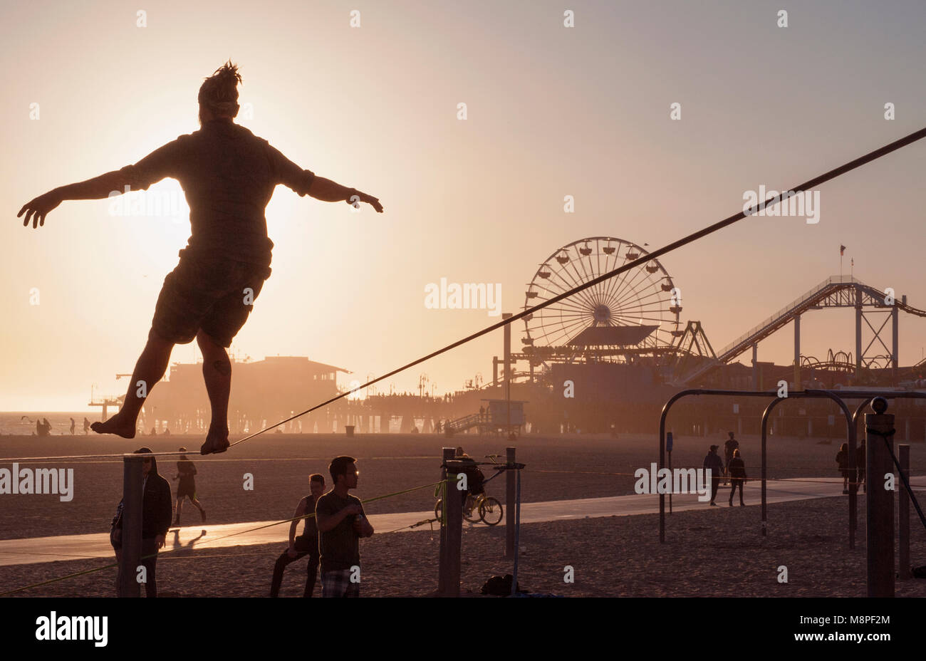 Tight rope practice on beach near the Santa Monica Pier, Los Angeles, CA - Stock Image