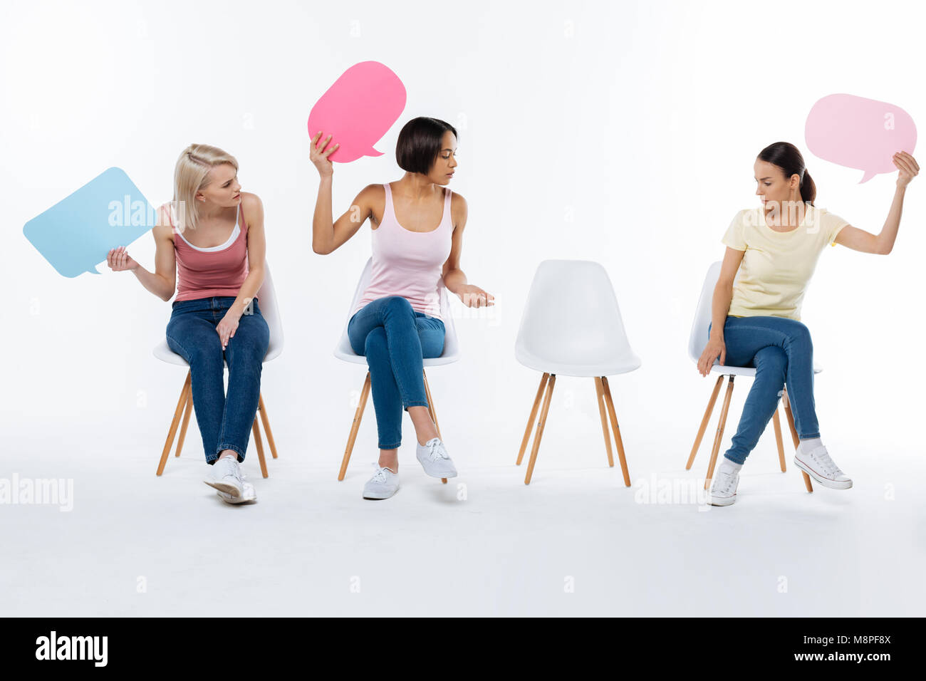 Positive young women looking at the chair - Stock Image
