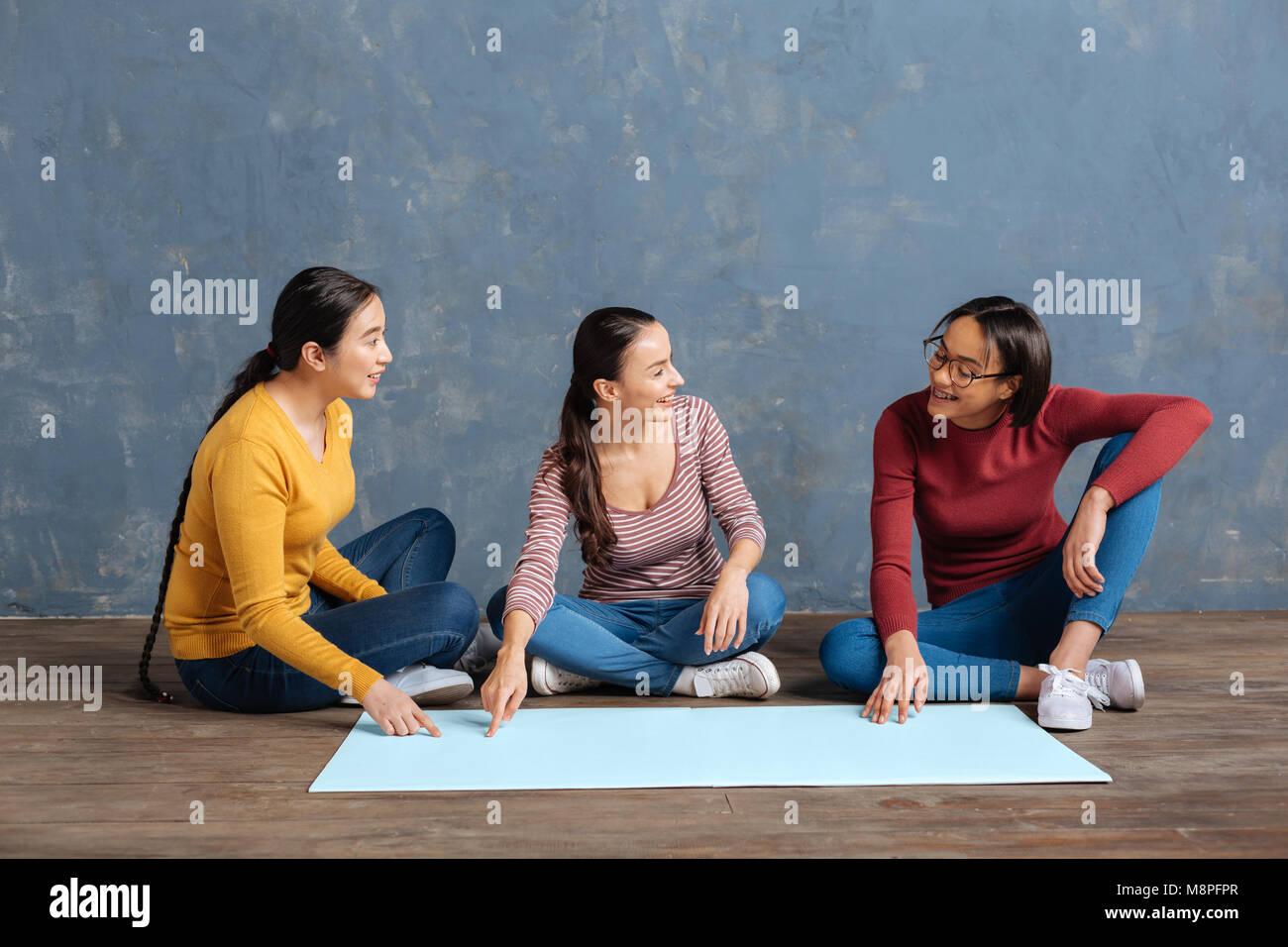 Cheerful happy women sitting on the floor - Stock Image