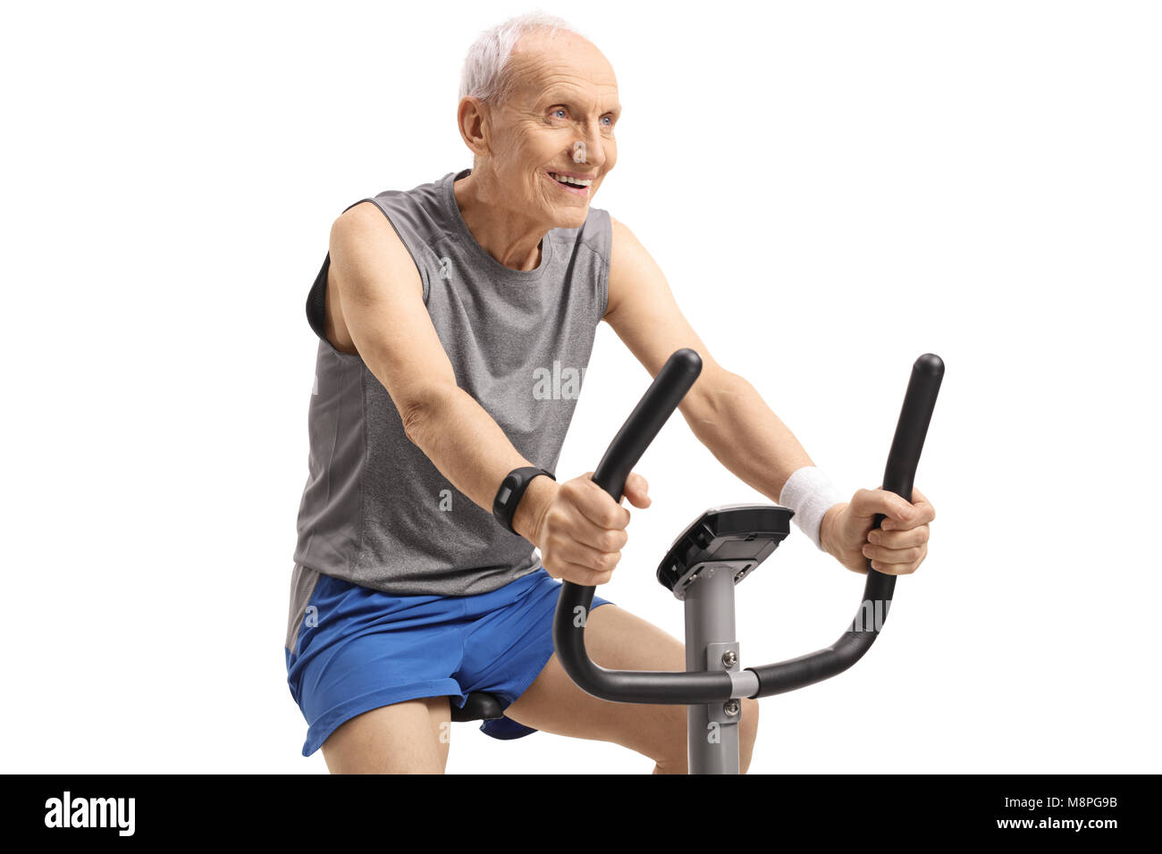 Senior working out on an exercise bike isolated on white background - Stock Image