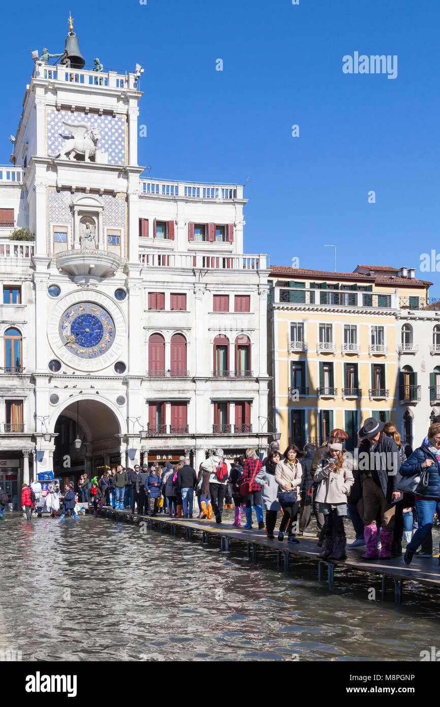 Tourists walking on passerelles  in front of the Clock Tower through a flooded St Marks Square, Piazza San Marco, Stock Photo