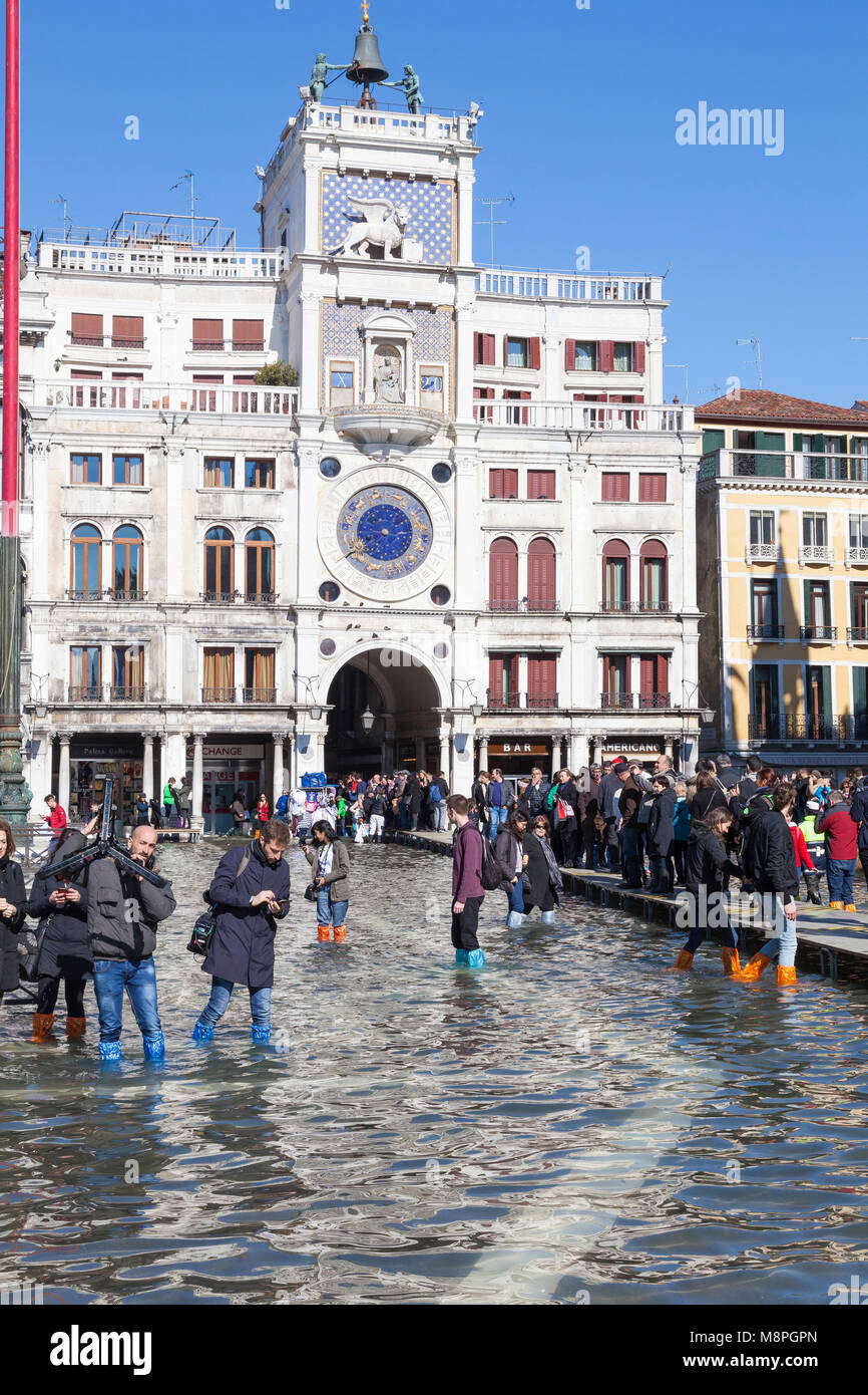 Tourists wading trough Acqua Alta flooding in Piazza San Marco, St Marks Square, in front of the Clock Tower, Venice, - Stock Image