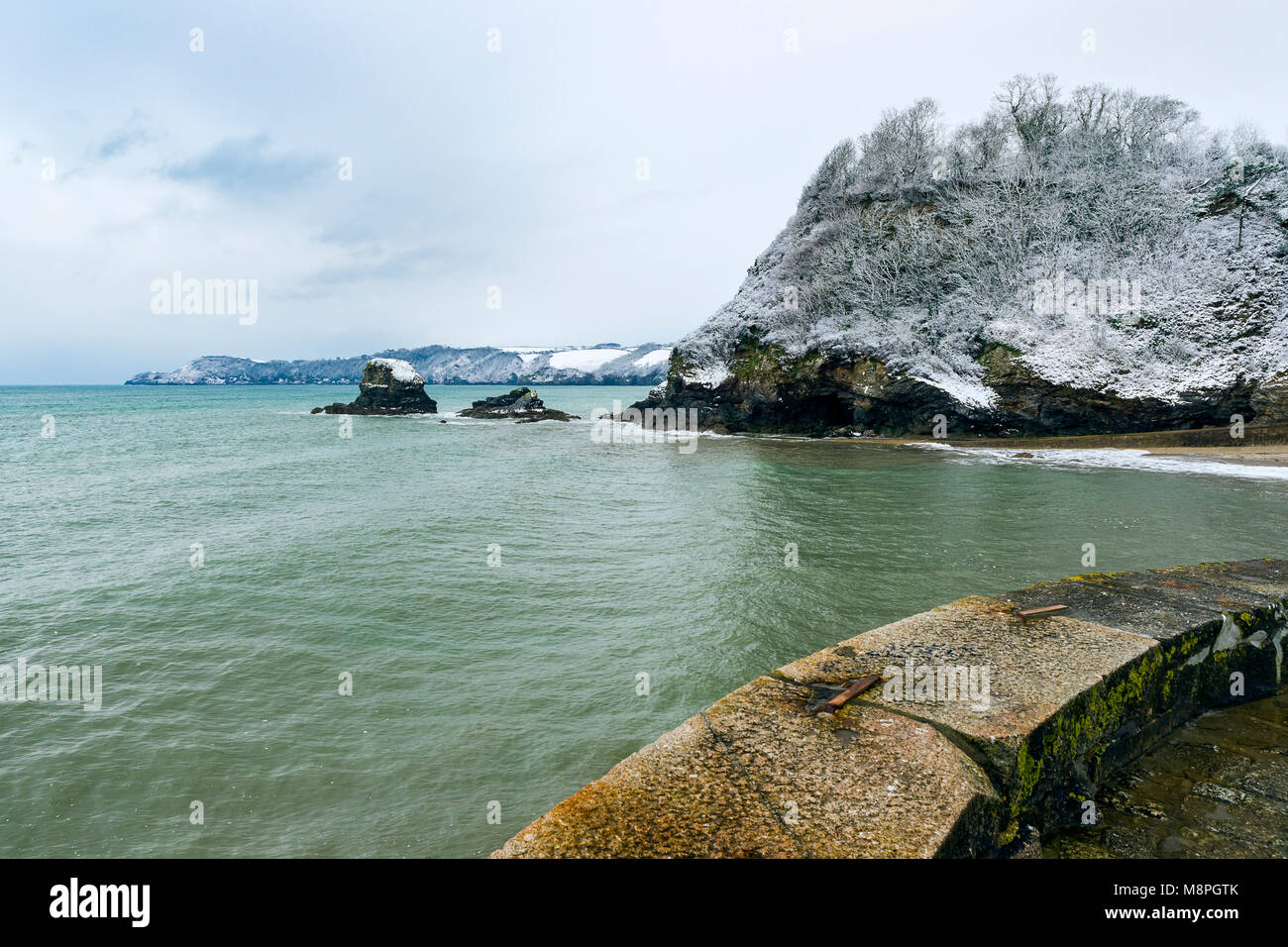Snow covers the cliff tops around the St Austell Bay area of Cornwall as seen from Charlestown Harbour wall. - Stock Image