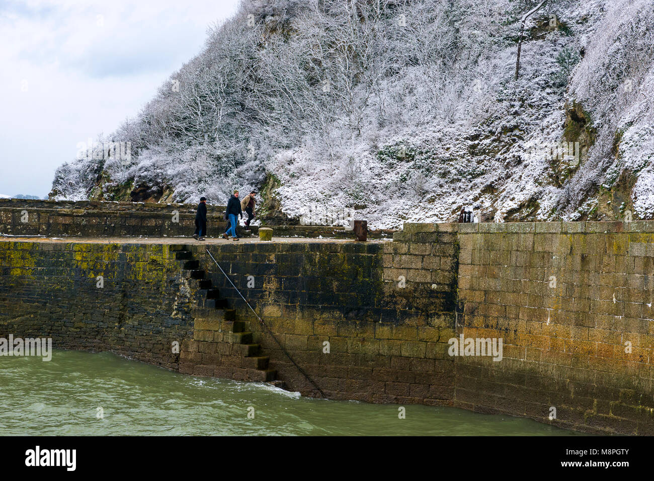 18/03/2018 Charlestown, Cornwall, UK, Editorial: Unknown members of the public walking along the harbour wall at - Stock Image