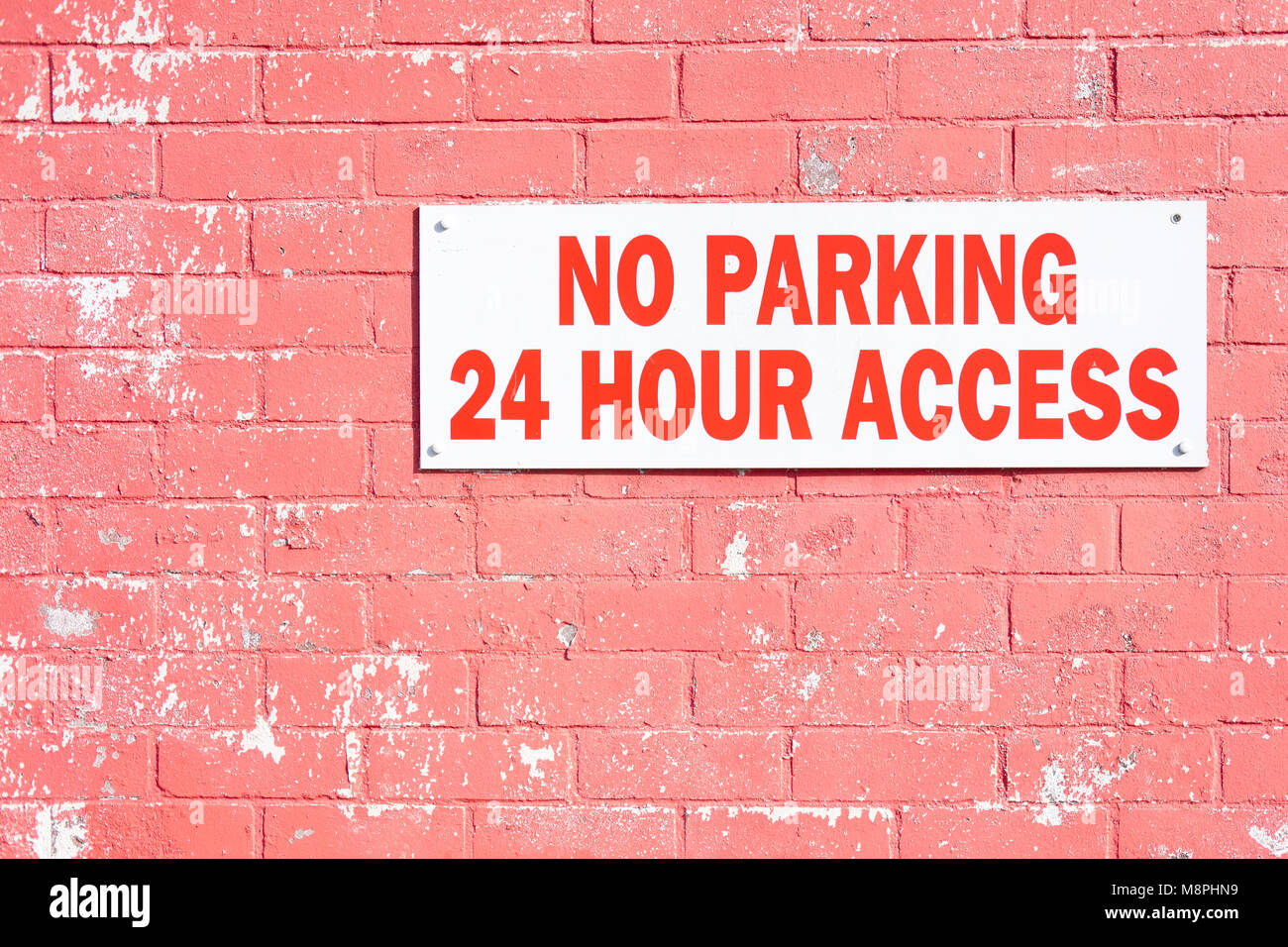 No parking 24 hour hr access required sign on red brick wall Stock Photo