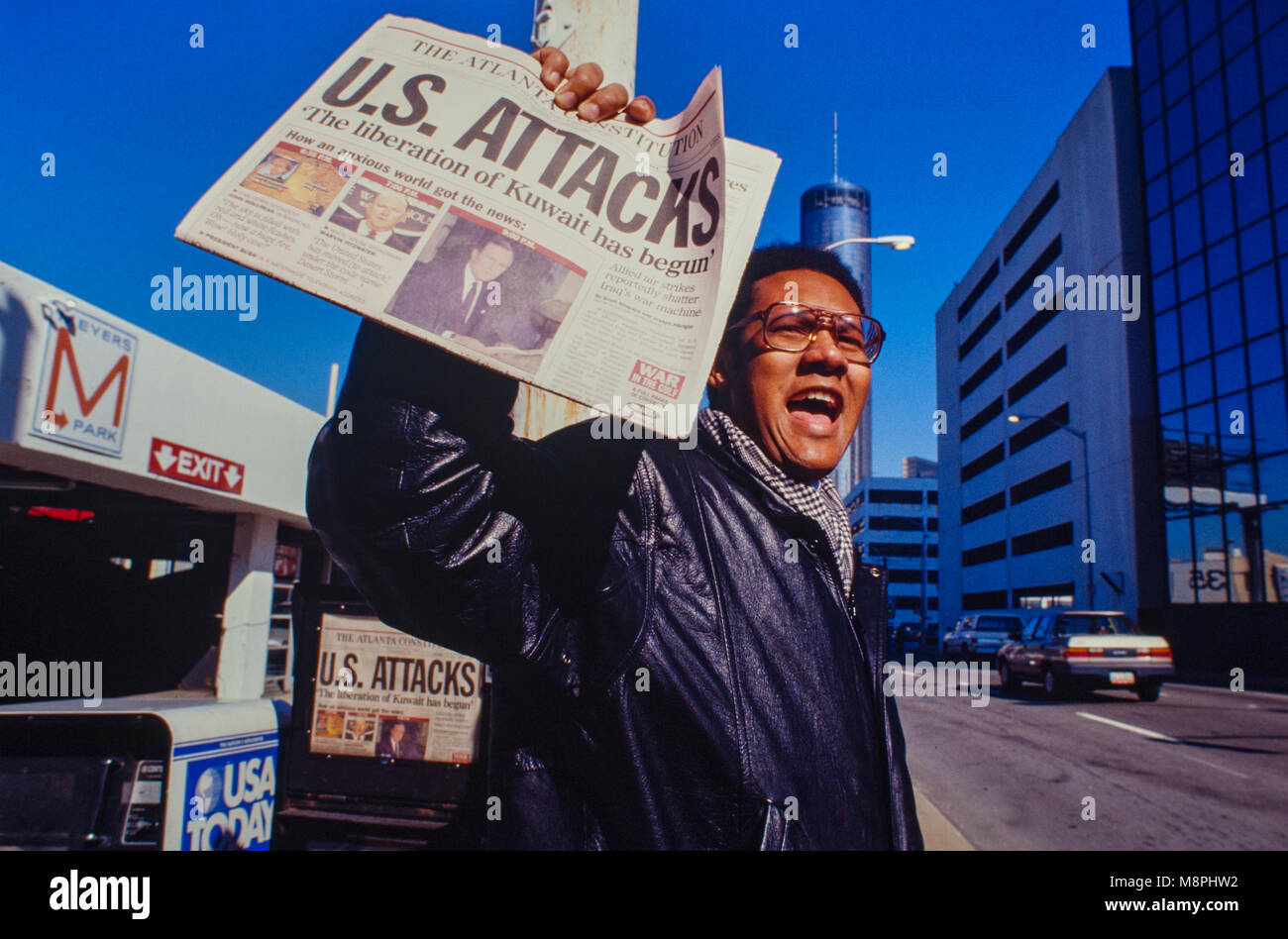 A newspaper vendor on an Atlanta, Georgia street corner holds a paper with the headline U.S. Attacks at the start - Stock Image